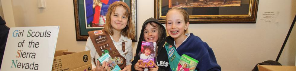 Girl scouts holding cookies