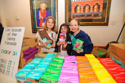 Girl scouts holding up boxes of cookies
